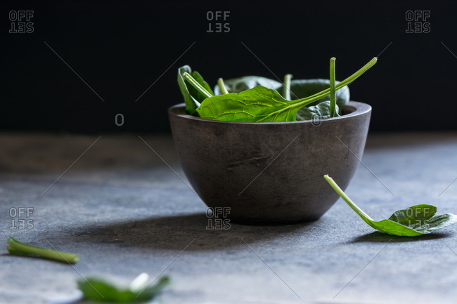 Fresh spinach on a rustic concrete crockery