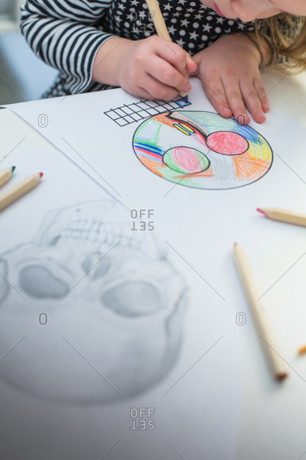 Girl coloring a simple sketch of a skull with a realistic skull at the background