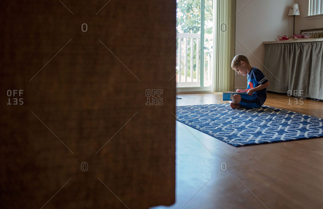 Boy reading book alone on floor