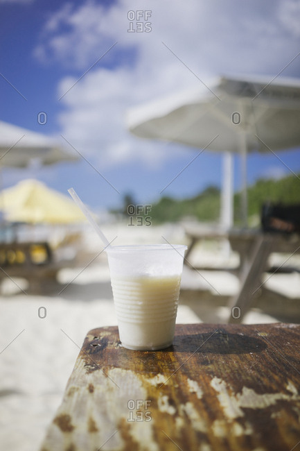 Drink in cup on table on beach