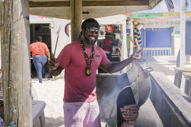Aguilla - January 15, 2017: Man grilling meat in tropical setting
