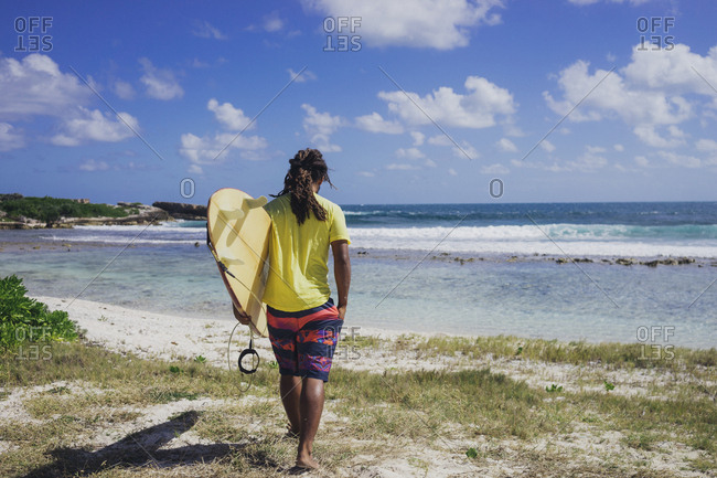 Man carrying surfboard on beach, Anguilla
