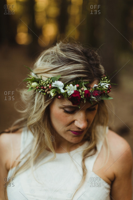 Woman with flowers in hair looking down