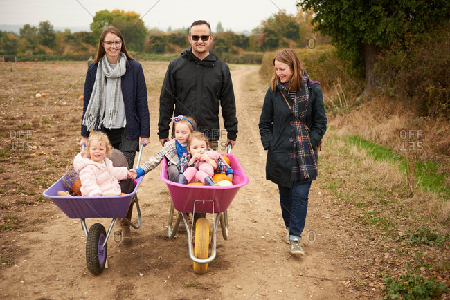 Portrait of parents pushing three girls in wheelbarrows along pumpkin field