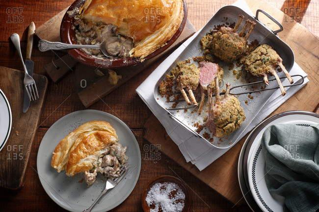 Bistro table with herb crusted lamb racks and rustic chicken pie