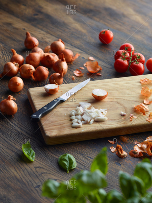 Fresh basil and cherry tomatoes with onions chopped on cutting board