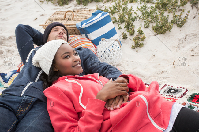 Young couple reclining on picnic blanket at beach, Western Cape, South Africa