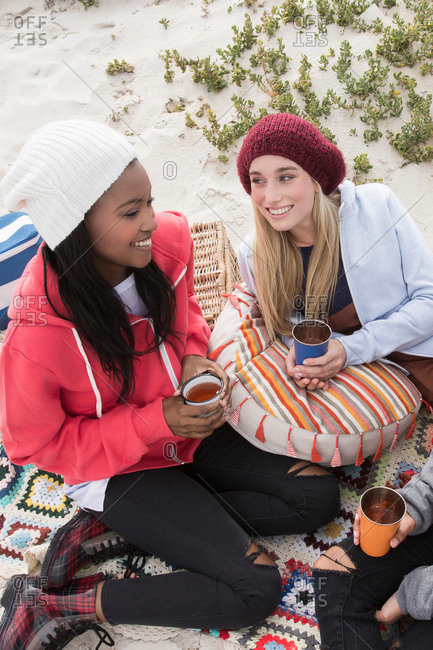 Three young women picnicking on beach, Western Cape, South Africa