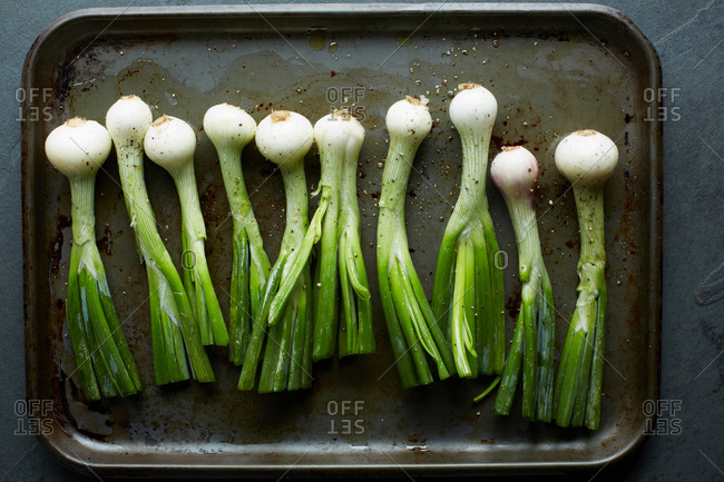 Overhead view of whole spring onions in roasting tin