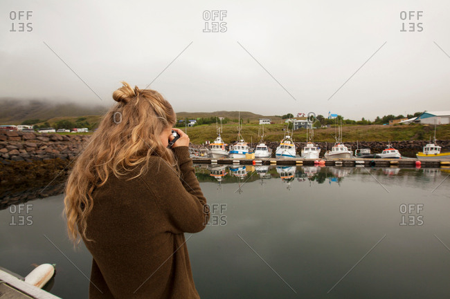 Rear view of young female tourist photographing lake harbor and boats, Seyoisfjorour, Iceland