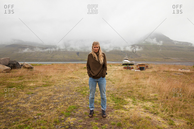 Portrait of young female tourist with hands in pockets in landscape, Seyoisfjorour, Iceland