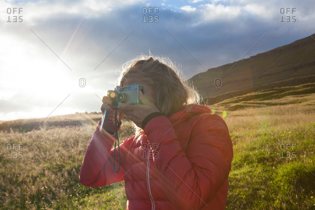 Female tourist photographing from sunlit hillside, Seyoisfjorour, Iceland