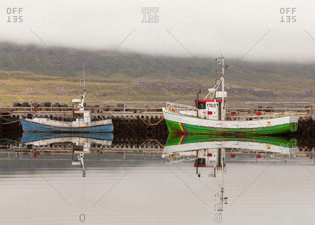 Two fishing boats moored on still lake, Seyoisfjorour, Iceland