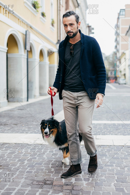 Mid adult man walking his dog in cobbled city street