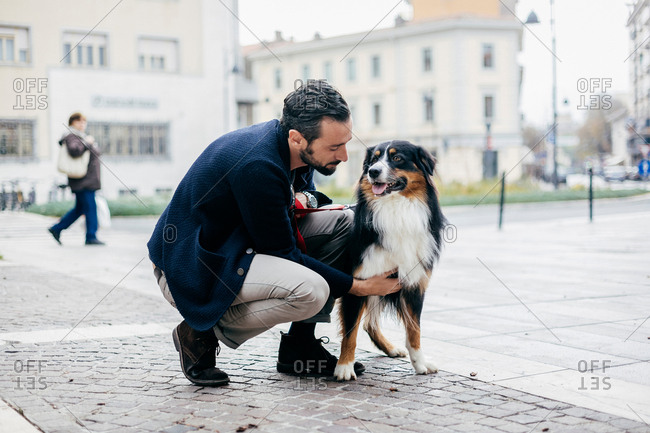 Mid adult man crouching to pet dog in cobbled city