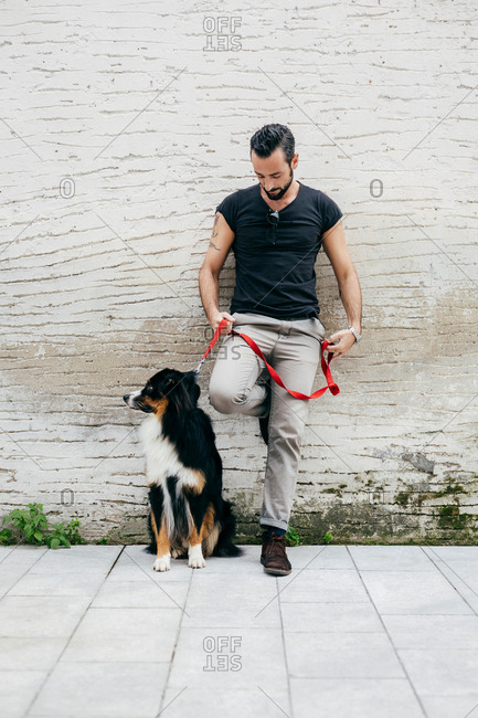 Mid adult man with dog leaning against wall