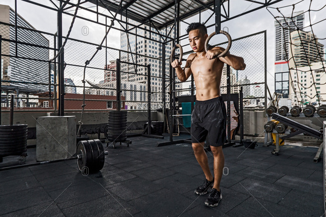 Young man preparing to train on exercise rings at rooftop gym in Bangkok