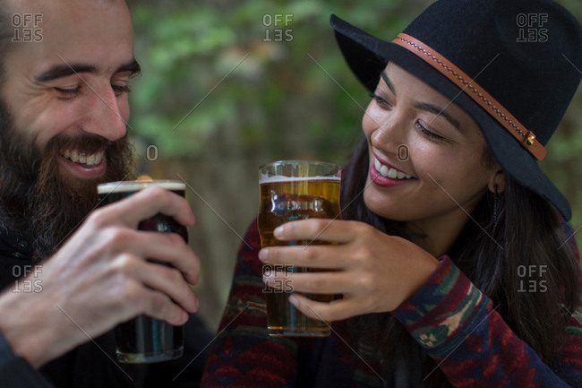 Young couple drinking beer in beer garden in evening, Brooklyn, New York, USA