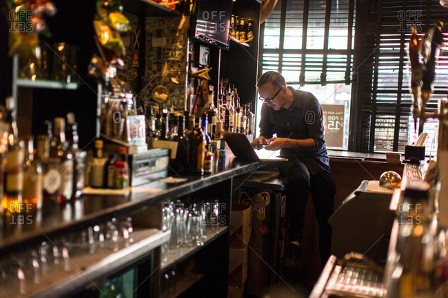 Barman typing on laptop at public house counter