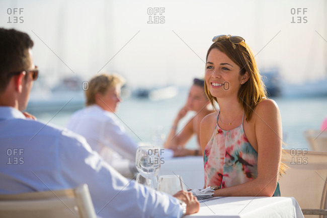 Couple chatting at waterfront restaurant, Majorca, Spain