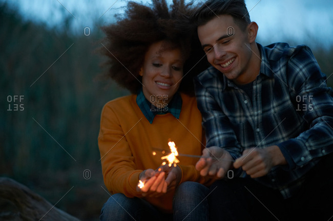 Young couple playing with sparklers in dunes at dusk