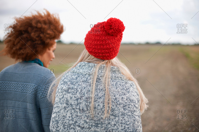 Rear view of two young women strolling in field