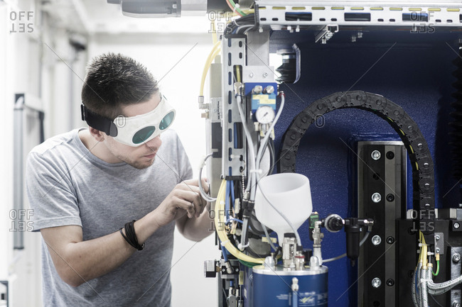 Engineer, wearing safety goggles, working in engineering plant