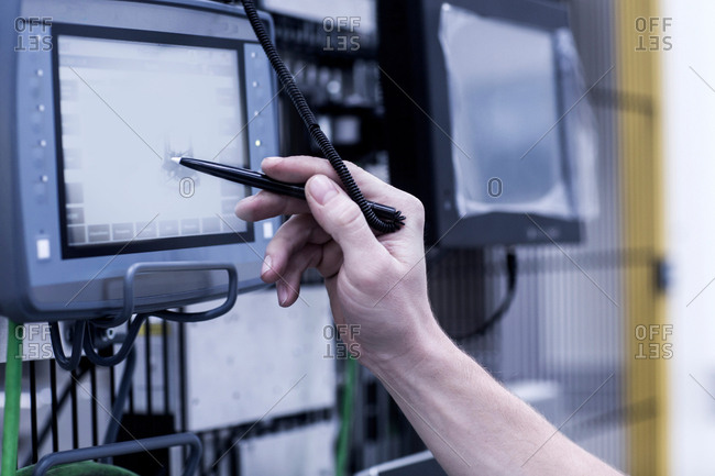Engineer in engineering plant, using stylus on screen, close-up
