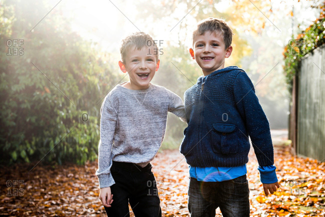Portrait of twin boys, outdoors, surrounded by autumn leaves, laughing