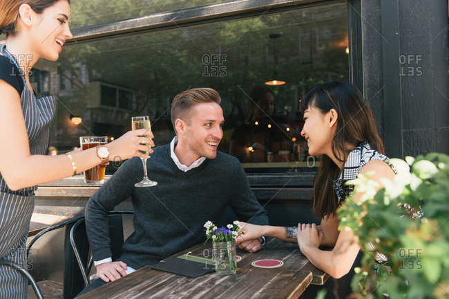 Young couple sitting outside bar, being served drinks by bar worker