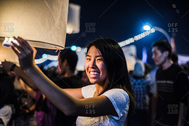 Young woman holding lit paper lantern waiting to release at Loy Krathong Paper Lantern Festival in Chiang Mai, Thailand