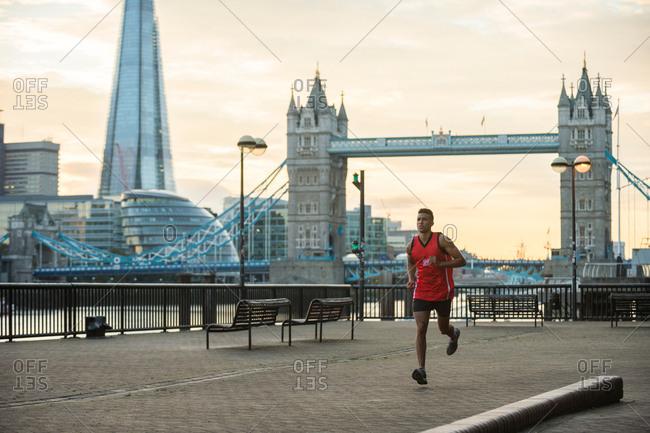 Man running by riverside at dawn, Wapping, London, UK
