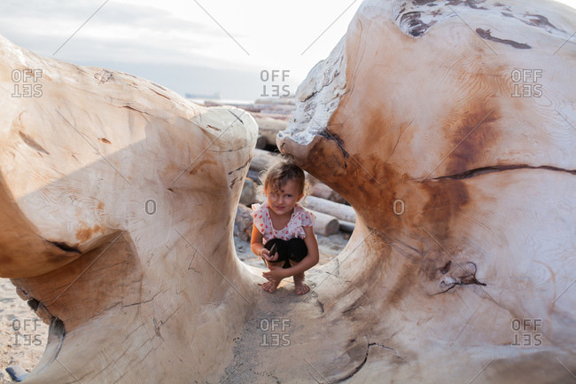 Little girl hiding in wood sculpture on beach, Vancouver, British Columbia, Canada
