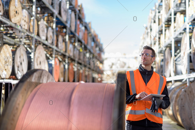Worker inspecting cable reels with digital pad at cable storage facility