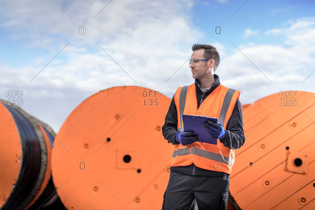 Worker inspecting electrical cable reels at cable storage facility, portrait