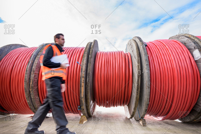 Worker walking past reels of electrical cable at cable storage facility
