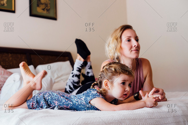 Woman lying on bed with toddler daughter watching TV