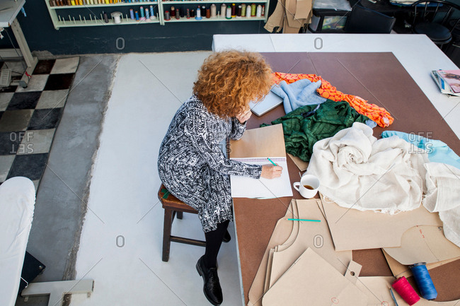 High angle view of mature female fashion designer drawing in sketchbook at workshop table