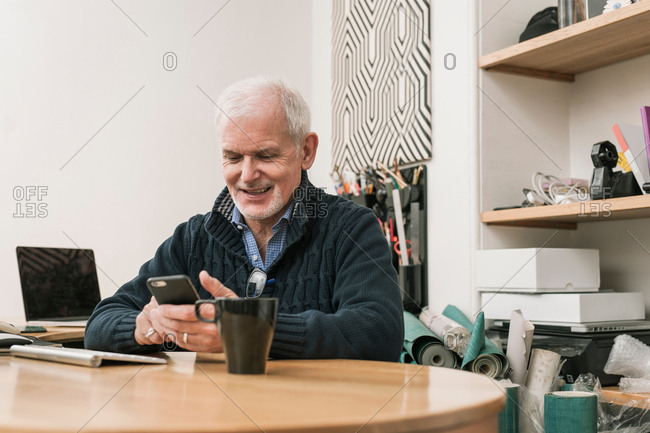 Senior man smiling, using mobile phone at work desk