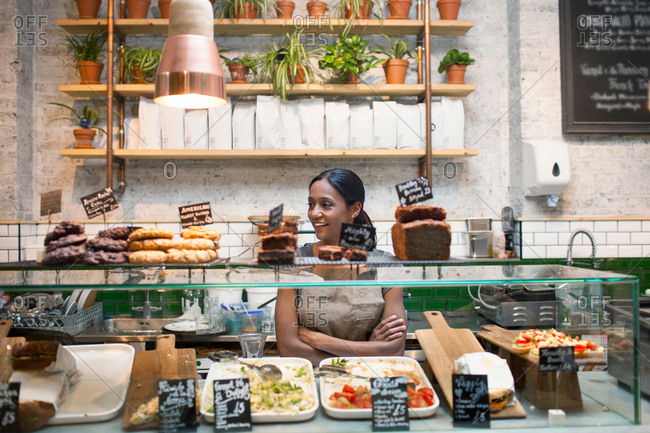 Waitress standing behind cafe display cabinet