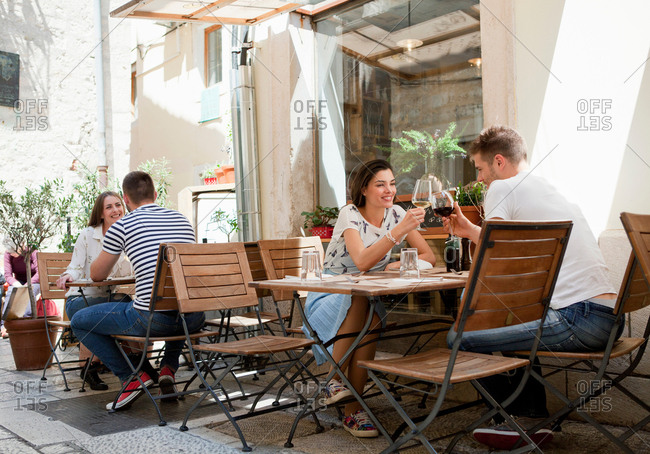 Young couples raising a wine toast at sidewalk restaurant, Split, Dalmatia, Croatia