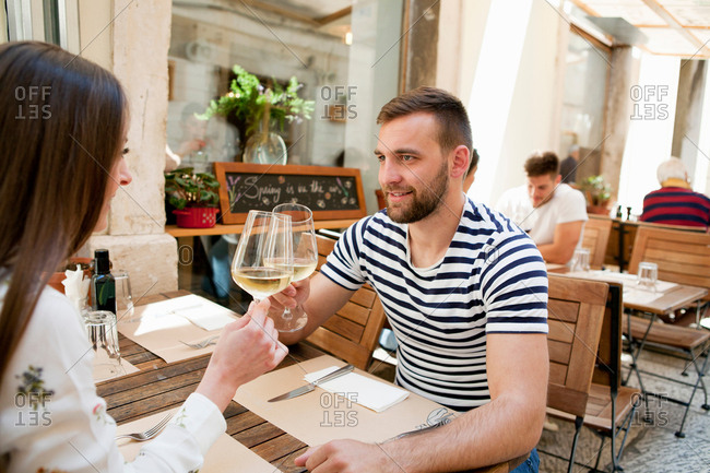 Young couple raising a wine toast at sidewalk restaurant, Split, Dalmatia, Croatia