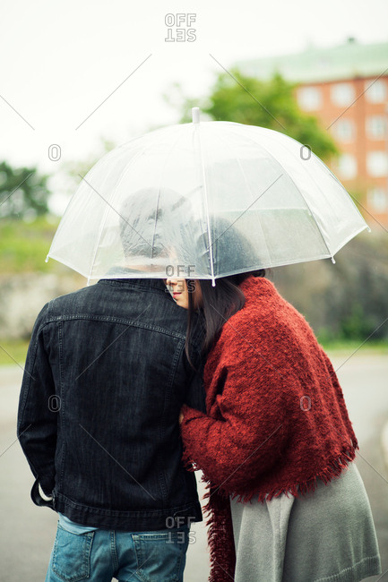 Rear view of romantic young couple under umbrella