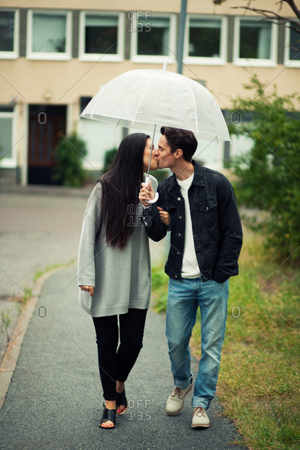 Romantic young couple kissing under umbrella