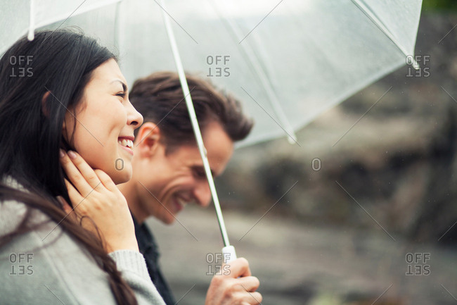 Romantic young couple strolling in rain