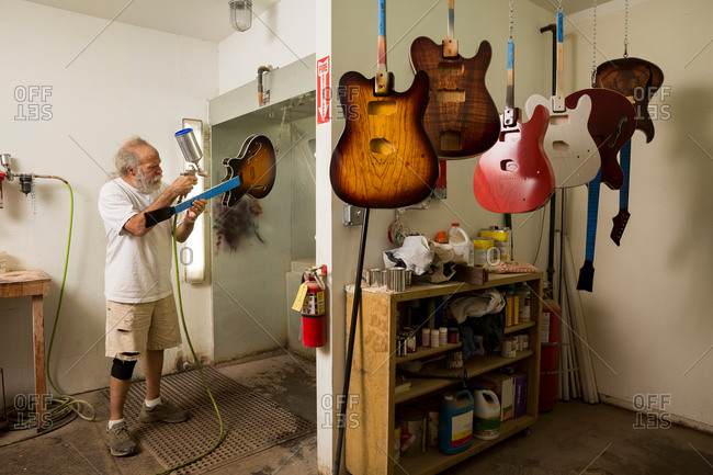 Guitar maker in workshop using spray gun to varnish guitar