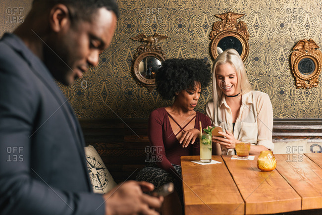 Friends sitting at table in pub looking at smartphone