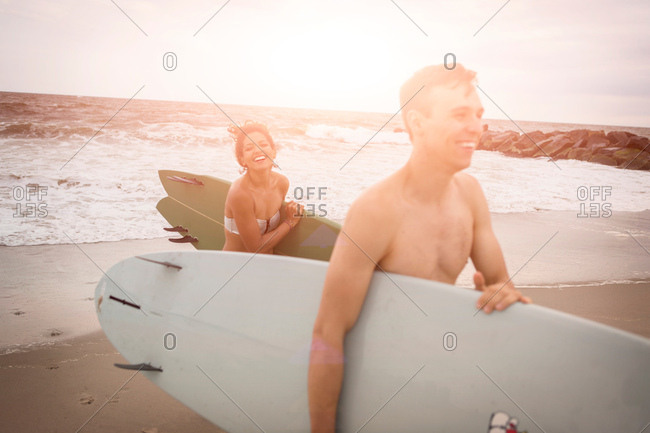 Young surfing couple carrying surfboards on Rockaway Beach, New York State, USA