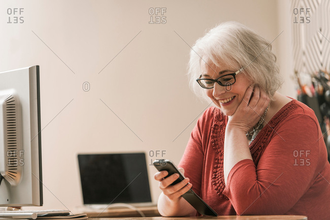 Woman smiling, using mobile phone at work desk