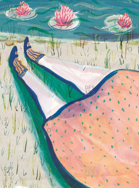 Woman's legs and feet lying on grass at edge of pond with lilies